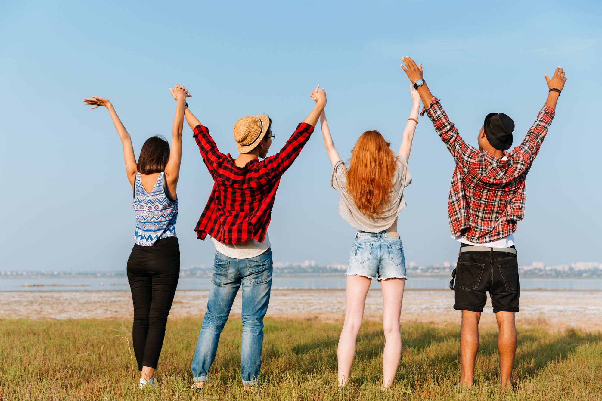 Back view of friends standing and holding raised hands outdoors